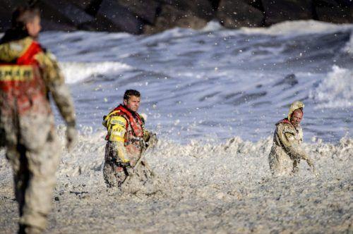 Rettungskräfte versuchen in der aufgewühlten See die Verunglückten zu bergen. AFP