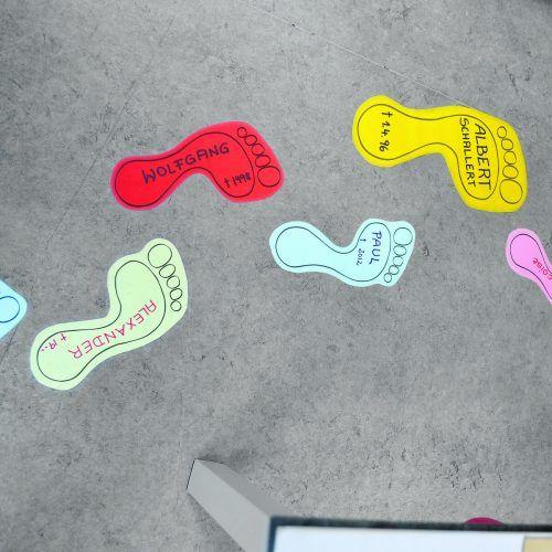 Farbige Fußabdrucke, mit den Namen der verstorbenen Klienten versehen.