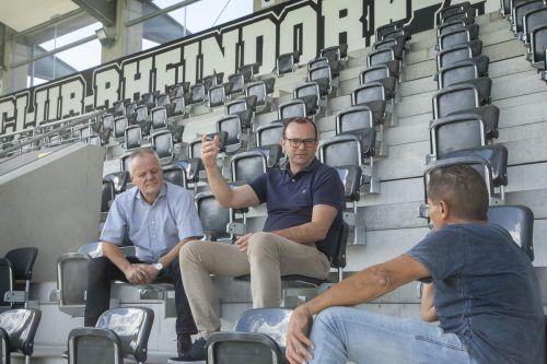 Auf der Fantribüne sitzend, sprechen Christoph Längle (Mitte) und Werner Gunz (links) über die Altacher Fußballpläne.Paulitsch