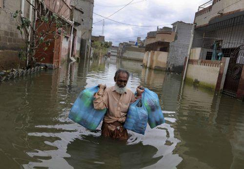 Dieser Mann kämpft sich mit seinen Einkäufen durch überschwemmte Straßen. AP