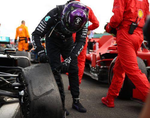 Lewis Hamilton inspiziert seinen demolierten Reifen. Der Weltmeister hatte sich trotz eines Pneuschadens in Silverstone zum Sieg gerettet.ap