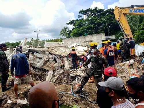 Rettungskräfte suchen in den Trümmern nach Verletzten. AFP