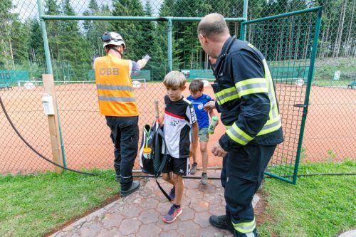 Sichtlich benommene Tennisplatzbesucher, darunter auch Kinder, wurden von der Feuerwehr aus der Gefahrenzone gebracht. hofmeister