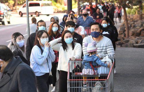 Zahlreiche Menschen warten vor einem Geschäft in Melbourne auf Einlass. In der Metropole gelten wieder strikte Maßnahmen. AFP