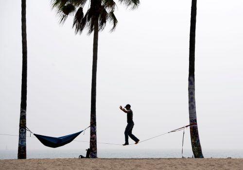 Ein Freizeitsportler balanciert in Venice Beach im US-Staat Kalifornien auf einem Seil, das zwischen zwei Palmen aufgespannt wurde. AFP
