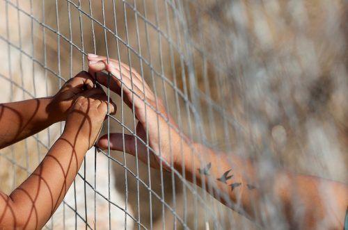 Im neuen provisorischen Flüchtlingslager auf der griechischen Insel Lesbos berührt eine Frau die Hände eines Kindes durch einen Zaun. reuters