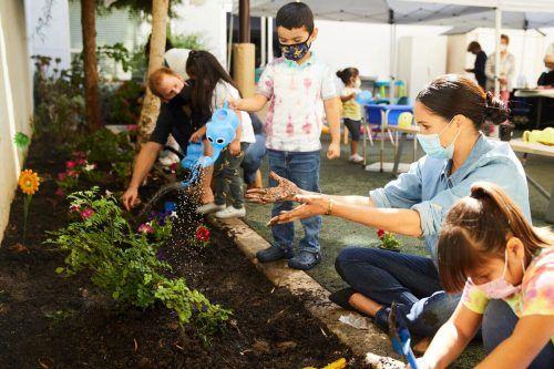 Prinz Harry und Meghan Markle haben gemeinsam mit Kindern Blumen gepflanzt.