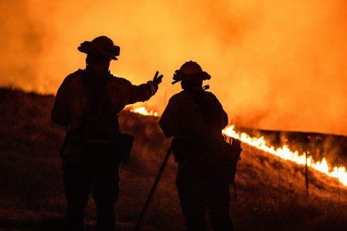 Zwei Feuerwehrleute beobachten am Stadtrand von Santa Rosa eine sich nähernde Feuerwand.AFP