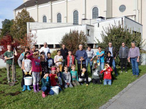 Gruppenbild der Beteiligten an der Blumenzwiebelaktion auf der Wiese, die im Frühjahr bunt erblühen soll.