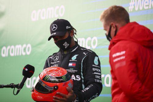 Mick Schumacher, Sohn von Rekordhalter Michael, überrascht Lewis Hamilton mit einem Helm seines Vaters. ap