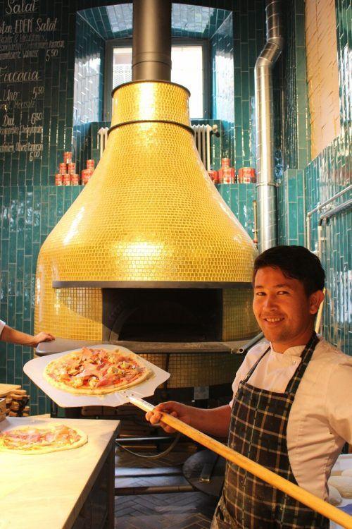 Mitten im Raum werkt Pizzabäcker Aijat am goldenen Ofen aus Neapel.