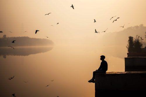 Schöner Ausblick trotz Smog: Ein Mann sitzt während des Sonnenaufgangs am Ufer des Yamuna Flusses im indischen Neu-Delhi. AFP
