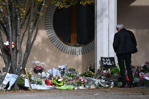 Vor der Schule in Conflans-Sainte-Honorine, nördwestlich von Paris, erinnern Blumen und Plakate an den brutal ermordeten Geschichtslehrer. AFP