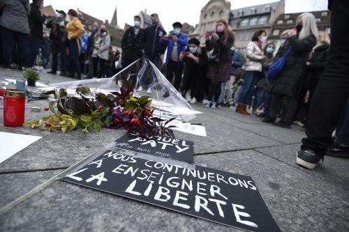 """Zahlreiche Menschen gedachten in Paris des getöteten Geschichtelehrers. Auf dem Plakat steht """"Wir werden weiterhin Freiheit lehren."""" reuters"""