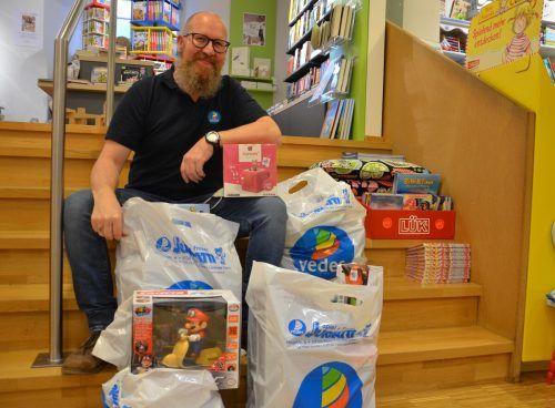 Adrian Juriatti hat von Kindern gewünschte Spielsachen in Plastiktaschen gepackt. HRJ