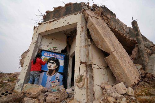 Der syrische Maler Aziz Asmar bemalt die Mauer eines zerstörten Hauses in der Provinz Idlib mit dem verstorbenen Fußballstar Diego Maradona. AFP