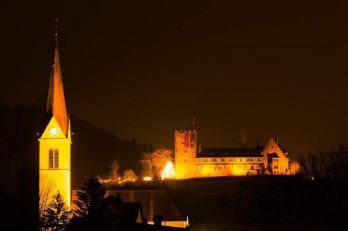 Die Pfarrkirche St. Nikolaus und Schloss Wolfurt werden in oranges Licht getaucht.MG Wolfurt, hapf