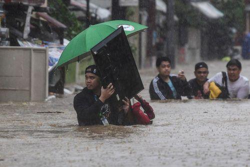 Diese Männer retten ihre Habseligkeiten aus ihren überschwemmten Häusern. AFP