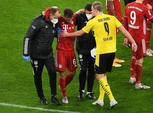 Dortmunds Erling Haaland versucht Bayerns Joshua Kimmich zu trösten, als dieser mit schmerzverzerrtem Gesicht das Spielfeld verlässt.gepa