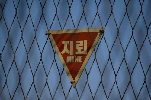Ein Schild an einem Zaun an der Grenze warnt vor Minen. AFP