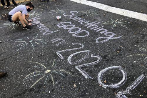 """""""Etwas Gutes ist 2020 passiert"""" schreibt diese Frau mit Kreide auf eine Straße in Harlem, New York. AP"""