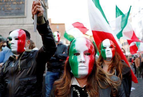 Mit Fahnen und Italien-Masken protestieren diese Menschen in Rom gegen die neuen Anti-Corona-Maßnahmen. reuters