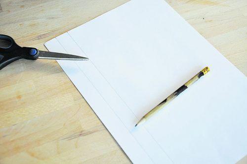 Schneidet aus dem weißen Papier zwei Streifen mit einer Breite von 2 cm aus.