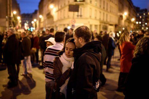 """Schockierte Menschen trösteten sich am 14. November 2015 nahe dem Lokal """"Le Carillon"""" - einem Schauplatz der Attacken. AFP, AP"""