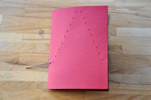 Stecht mit der Nadel Löcher in die Karte, sodass der Umriss eines Weihnachtsbaumes entsteht.