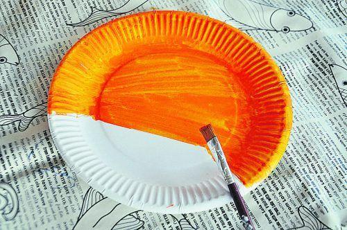 Zuerst malt ihr einen Teller mit Wassermalfarbe orange an und lasst ihn trocknen.