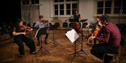 """Filippa Gojo mit dem Ensemble von Klaus Christa bei der Uraufführung des Werks """"Die (einfache) Liebe"""" im Pförtnerhaus in Feldkirch. Videostill"""