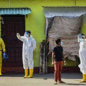 """<p class=""""factbox"""">Gesundheitsmitarbeiter in Schutzanzügen warten in Colombo, Sri Lanka, auf Menschen, die sich auf das Coronavirus testen lassen. AFP</p>"""