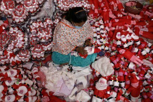 In ihrer Werkstatt in der indischen Metropole Kolkata stellt eine Frau Weihnachtsmann-Puppen her. reuters