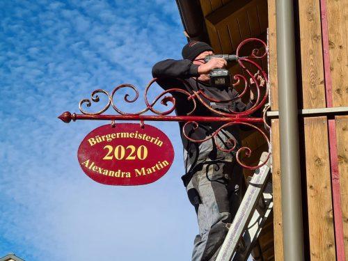 Kunstschlosser Johann Gruber befestigte das handgefertigte Bürgermeisterschild.SG