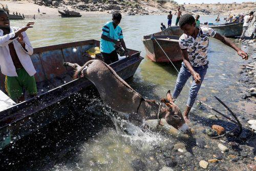 Mit all ihrem Hab und Gut flüchten Äthiopier vor den Kämpfen in Tigray. Ein Boot bringt sie über einen Fluss in den Sudan. REUTERS