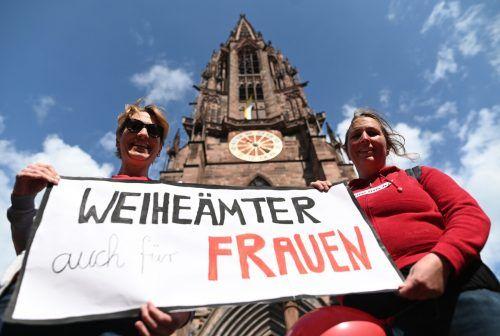 """Zwei Frauen der Initiative Maria 2.0 in der Erzdiözese Freiburg halten vor dem Münster ein Banner mit der Aufschrift """"Weiheämter auch für Frauen"""". APA"""