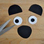 """<p class=""""bodytext"""">Aus schwarzem und weißem Tonpapier schneidet ihr Schnauze, Innenohre und Augen aus.</p>"""