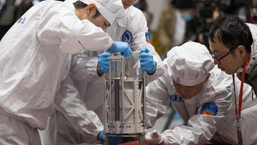 Chinesische Wissenschafter wiegen die Gesteinsproben.dpa