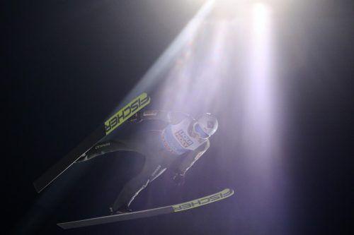 Der Tourneeführende Kamil Stoch im Scheinwerferlicht während seines Qualifikationssprunges für das Abschlussspringen in Bischofshofen.ap
