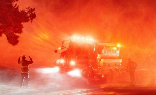 Einsatzkräfte der Feuerwehr kämpfen auf der Interstate 210 in Sylmar im US-Staat Kalifornien gegen sich ausbreitende Waldbrände. AFP