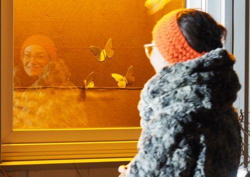 Künstlerin Martina Feichtinger blickt auf ihre fliegenden Monarchfalter.Adlassnigg