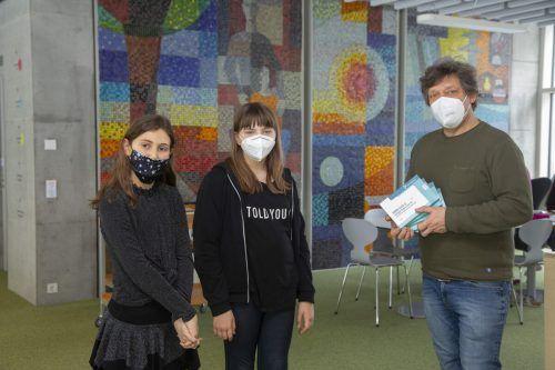 Lara und Emilie (v.l.) erhalten aus den Händen von Lehrer Erich Hollenstein den Corona-Selbsttest.VN/Paulitsch