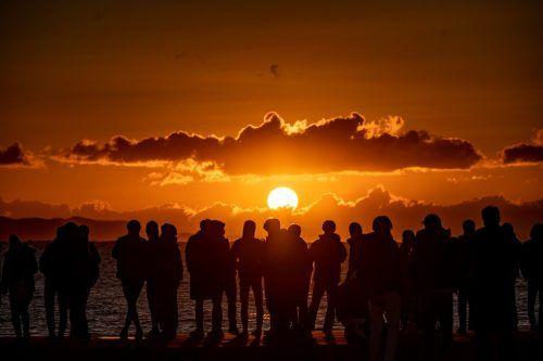 Menschen versammeln sich am Strand von Chigasaki in Japan, um den atemberaubenden Sonnenaufgang an Neujahr zu betrachten. AFP