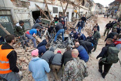 Menschen versuchen den Schutt vor den Häusern in Petrinja wegzuschaffen. AFP