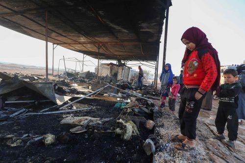Nach einem Brand im Camp Tal Karamah im syrischen Idlib stehen Flüchtlingskinder vor den Überresten ihres Zeltes. AFP