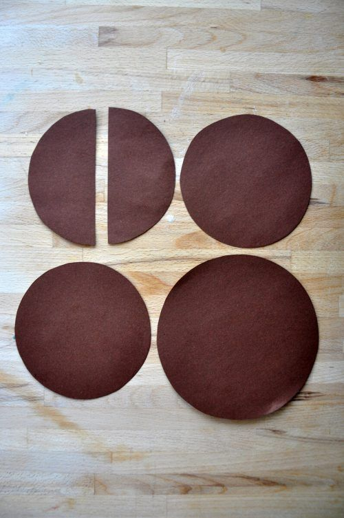 Schneidet aus dem braunen Papier einen großen (14 cm Durchmesser) und drei kleinere (12 cm Durchmesser) Kreise aus – einen der kleinen Kreise schneidet ihr in der Mitte durch.