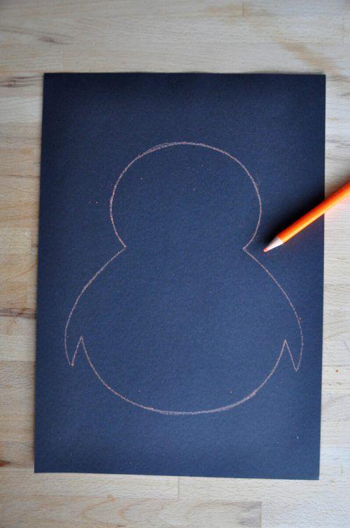 Zeichnet den Umriss eines Pinguins auf das schwarze Papier.