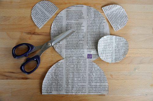 Zeichnet Kopf, Nase, Körper und Ohren auf das Zeitungspapier auf und schneidet die Teile aus.