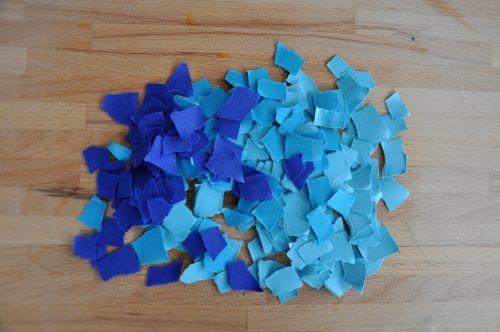 Zerreißt das blaue Papier in viele kleine Schnipsel.