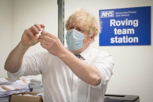Der Regierungschef betrachtet in einem Impfzentrum in London eine Impfdosis von AstraZeneca. AFP